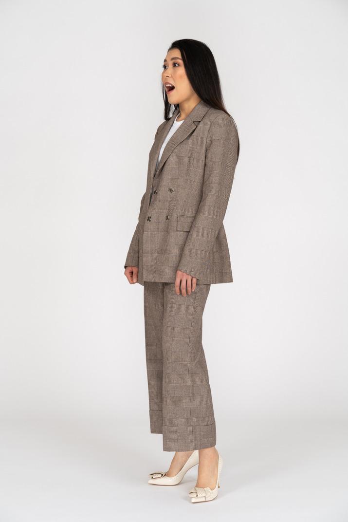 Dreiviertelansicht einer überraschten jungen dame im braunen business-anzug