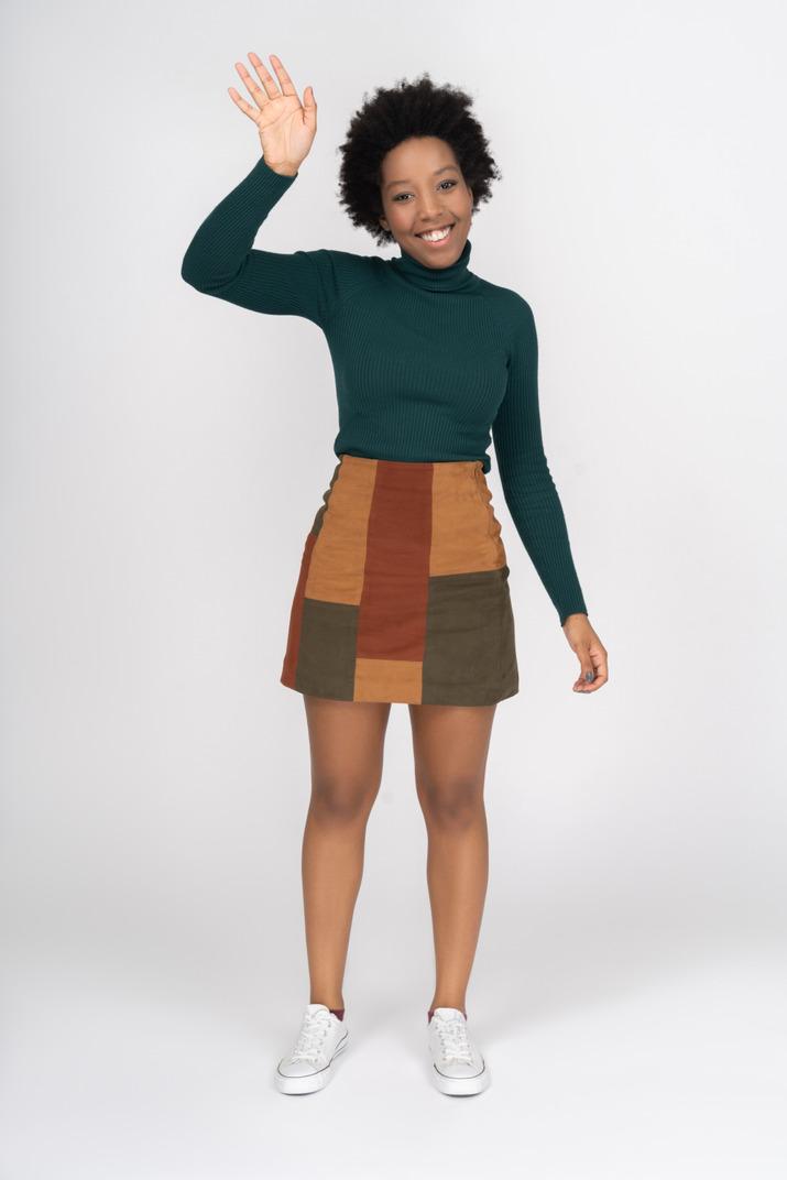 Cute cheerful african girl waving hello