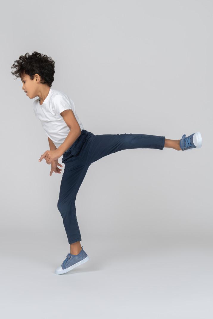 A boy standing on one leg
