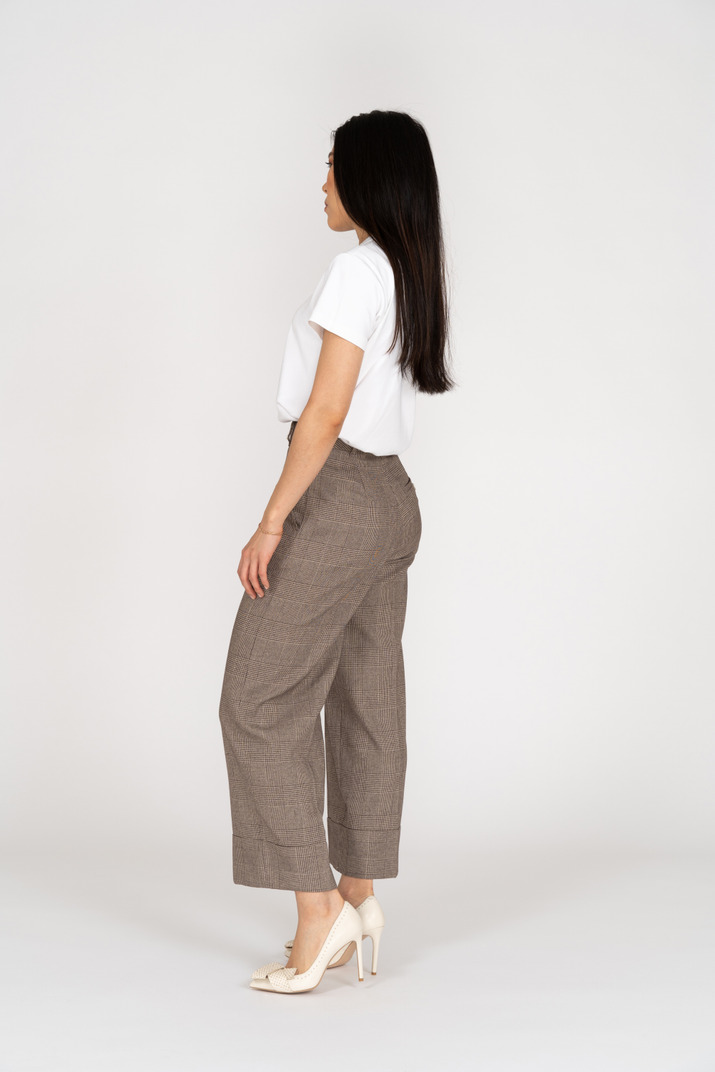 Side view of a young woman in breeches standing still
