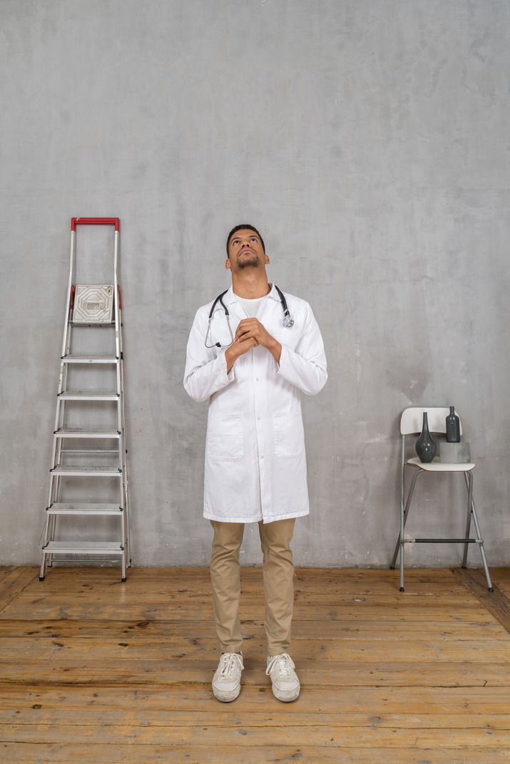 Front view of a praying young doctor standing in a room with ladder and chair