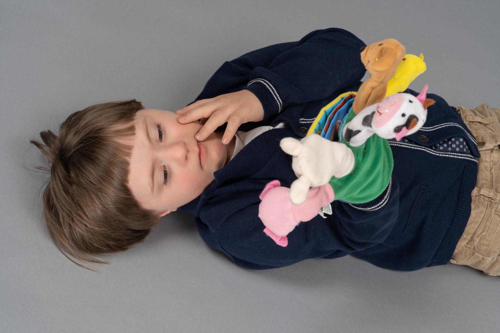 Liegender kleiner junge, der aufmerksam auf flauschige spielzeuge schaut