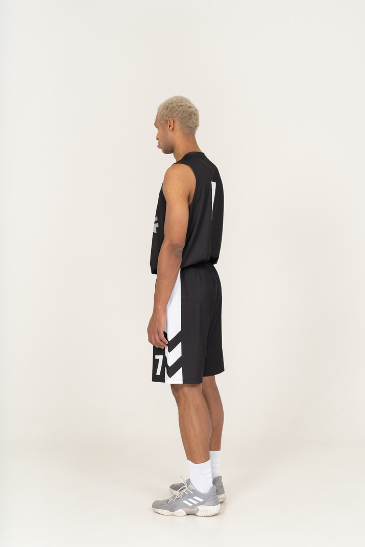 Three-quarter back view of a pouting young male basketball player