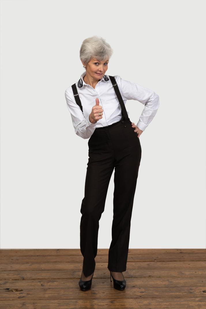 Vorderansicht einer alten unzufriedenen frau in bürokleidung, die einen daumen nach oben zeigt