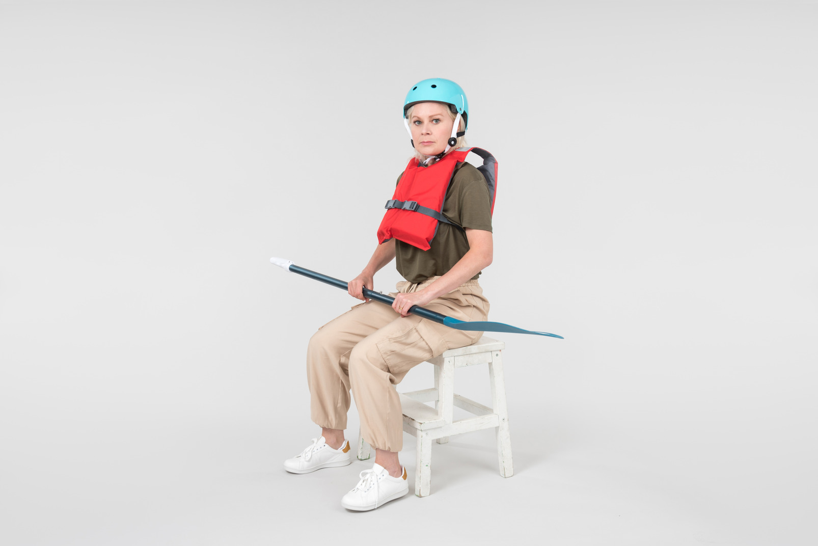 Mature woman wearing life vest and blue helmet holding paddle