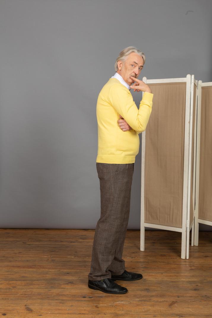 Seitenansicht eines alten mannes, der finger beim betrachten der kamera beißt