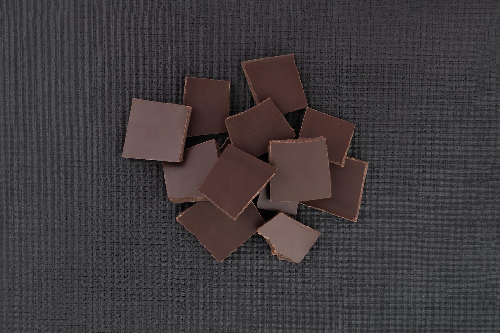 Dunkle schokolade auf schwarzem hintergrund abgestürzt