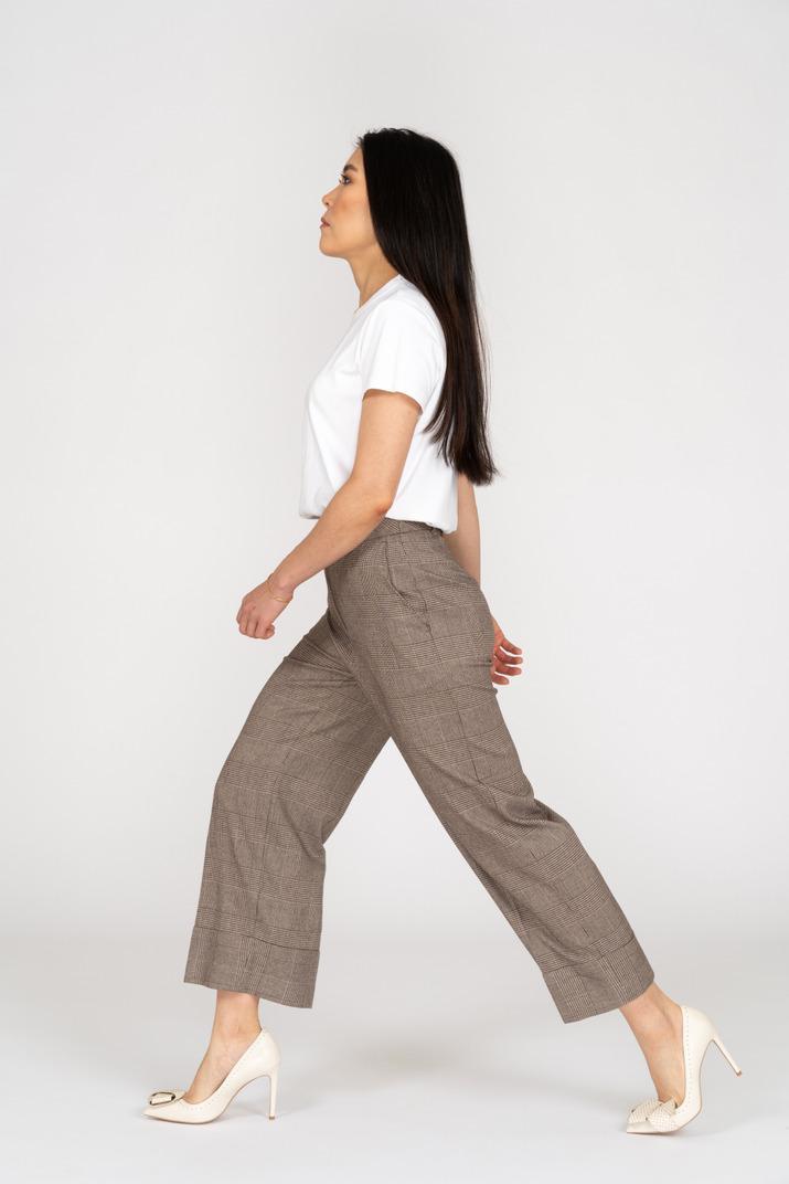Seitenansicht einer wandelnden jungen dame in reithose und t-shirt