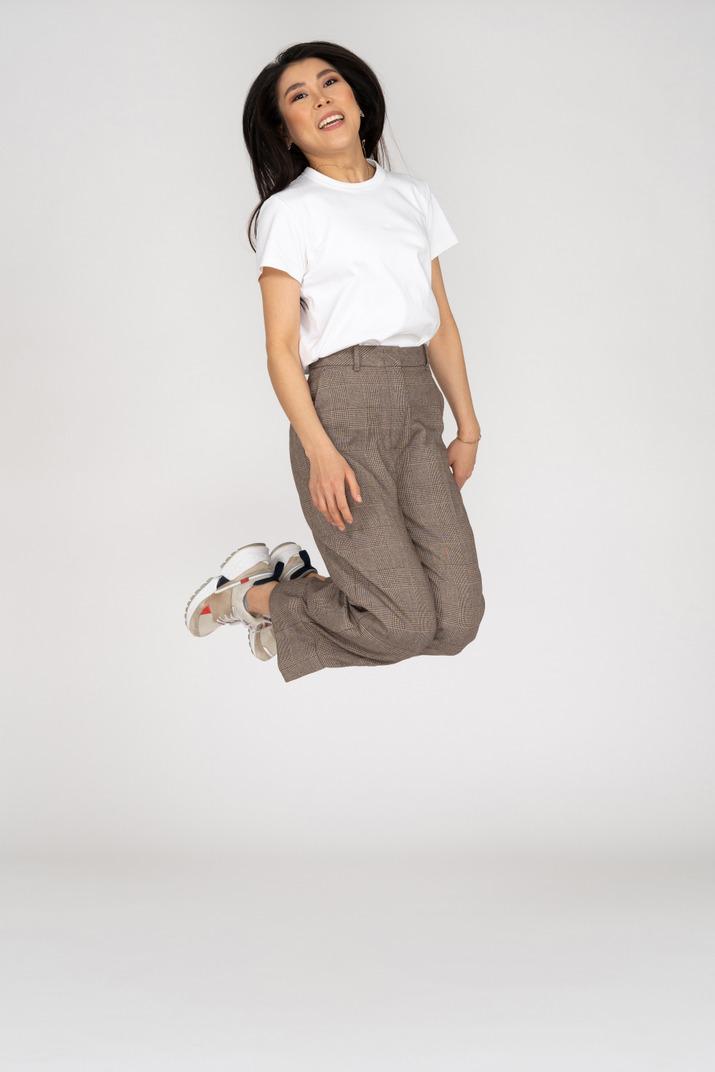 Vorderansicht einer springenden jungen dame in reithosen und t-shirt, die knie beugen