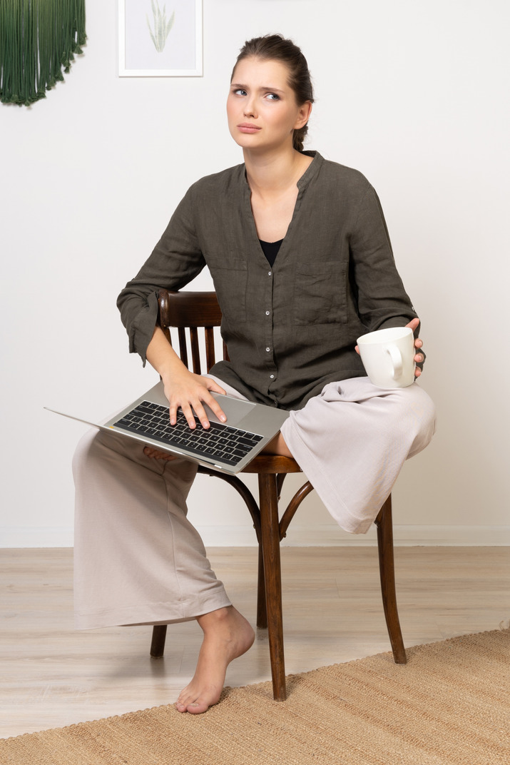 Front view of a confused young woman wearing home clothes sitting on a chair with a laptop & coffee cup
