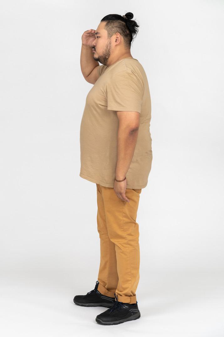Plump asian man saluting in profile