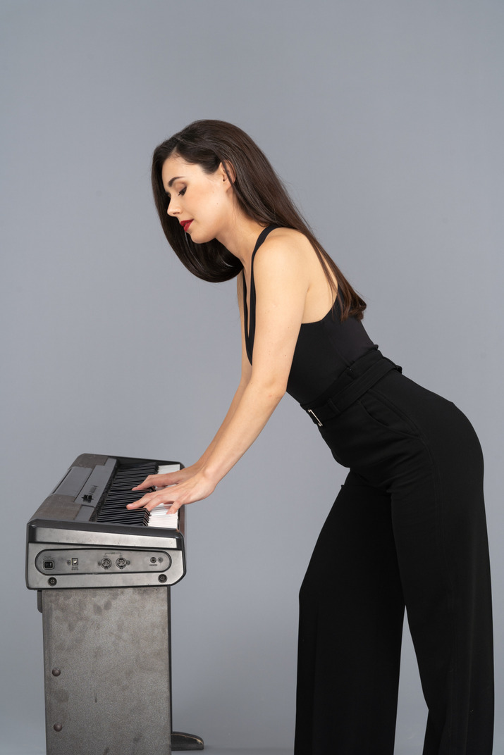 Vista lateral, de, un, señorita, en, traje negro, tocar el piano