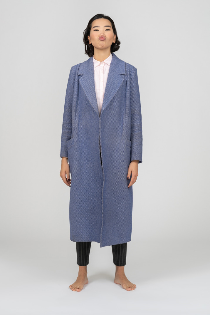 Young asian woman in long blue coat sending air kiss