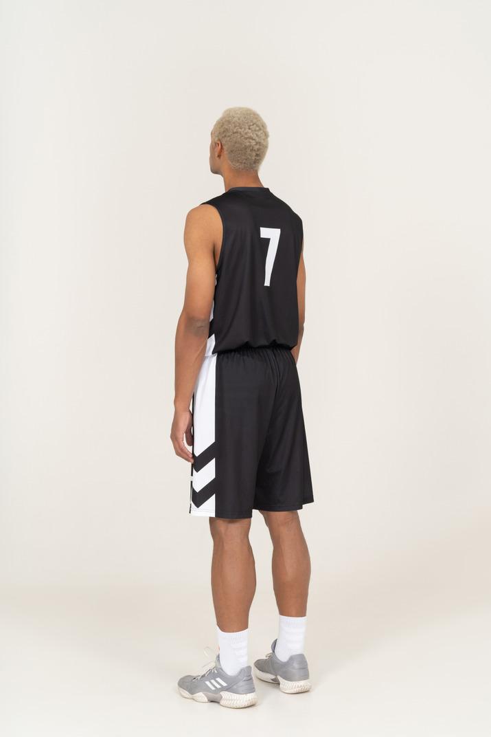 Vista traseira a três quartos de um jovem jogador de basquete, parado