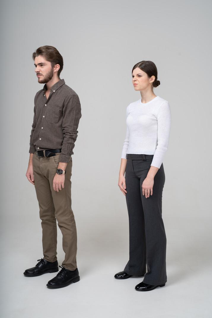 Dreiviertelansicht eines unzufriedenen jungen paares in bürokleidung, das brauen strickt