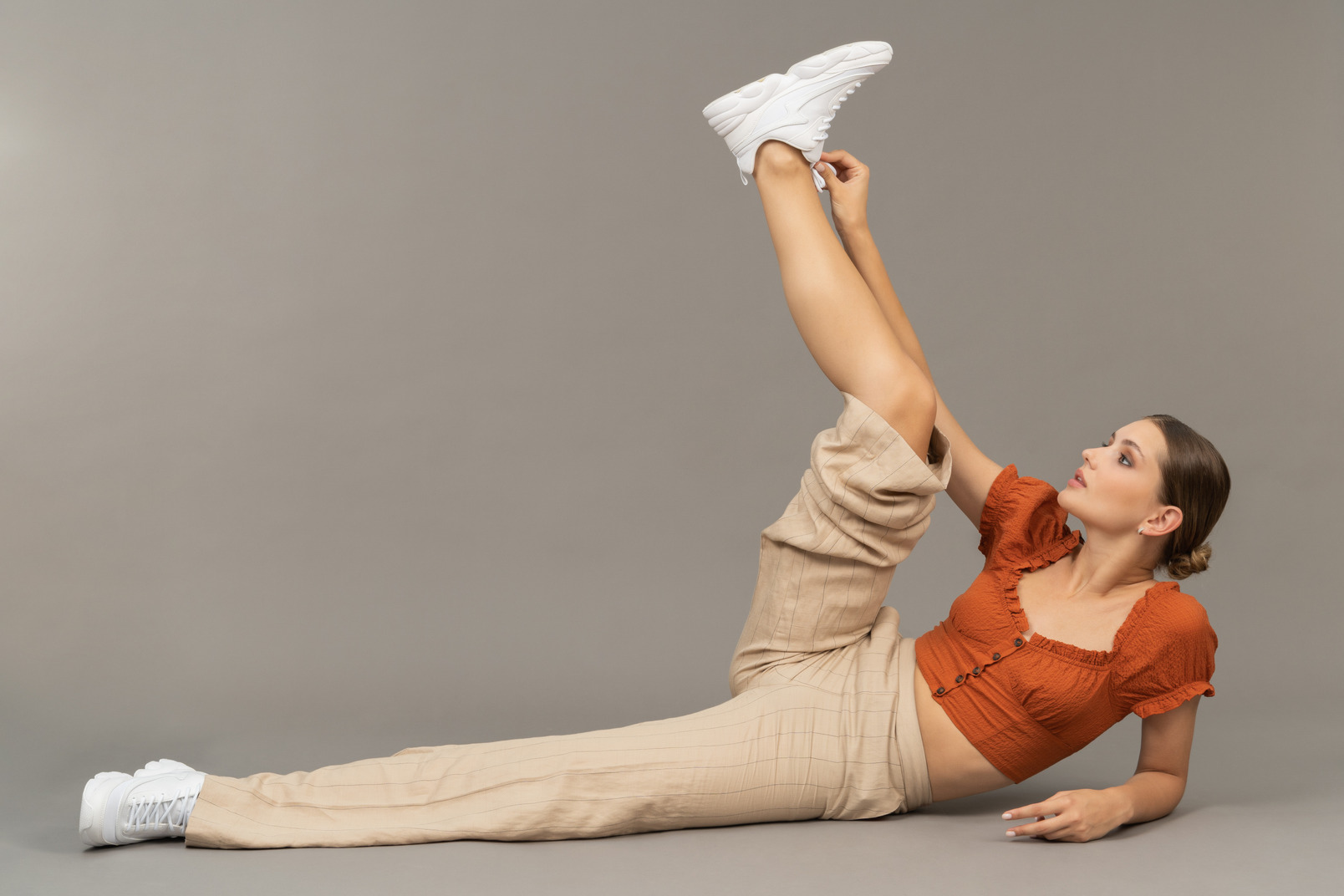 Young woman lies down and puts her leg up