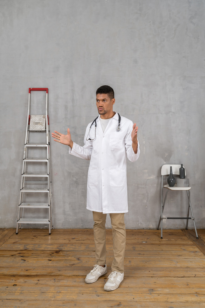 Three-quarter view of a young gesticulating doctor standing in a room with ladder and chair