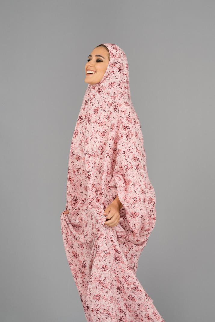 Lächelnde muslimische frau, die ein gebetskleid trägt