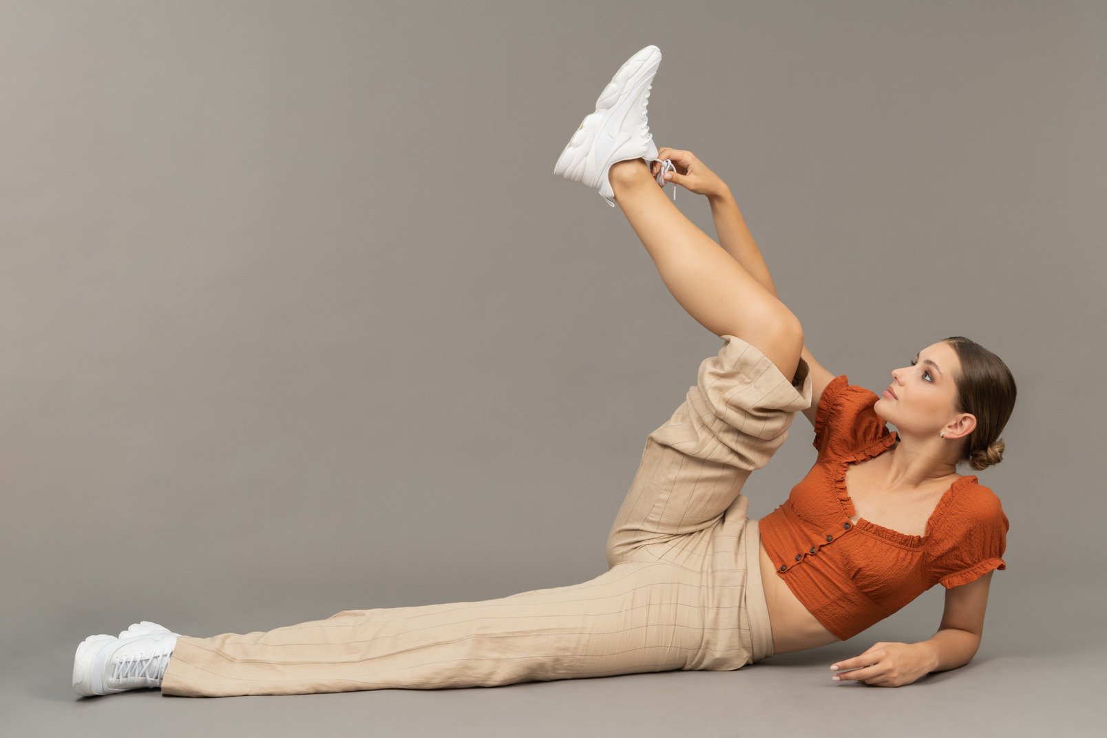 Young woman lies down with her leg up