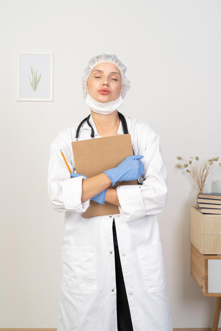 鉛筆とタブレットを保持しているキス若い女性医師の正面図
