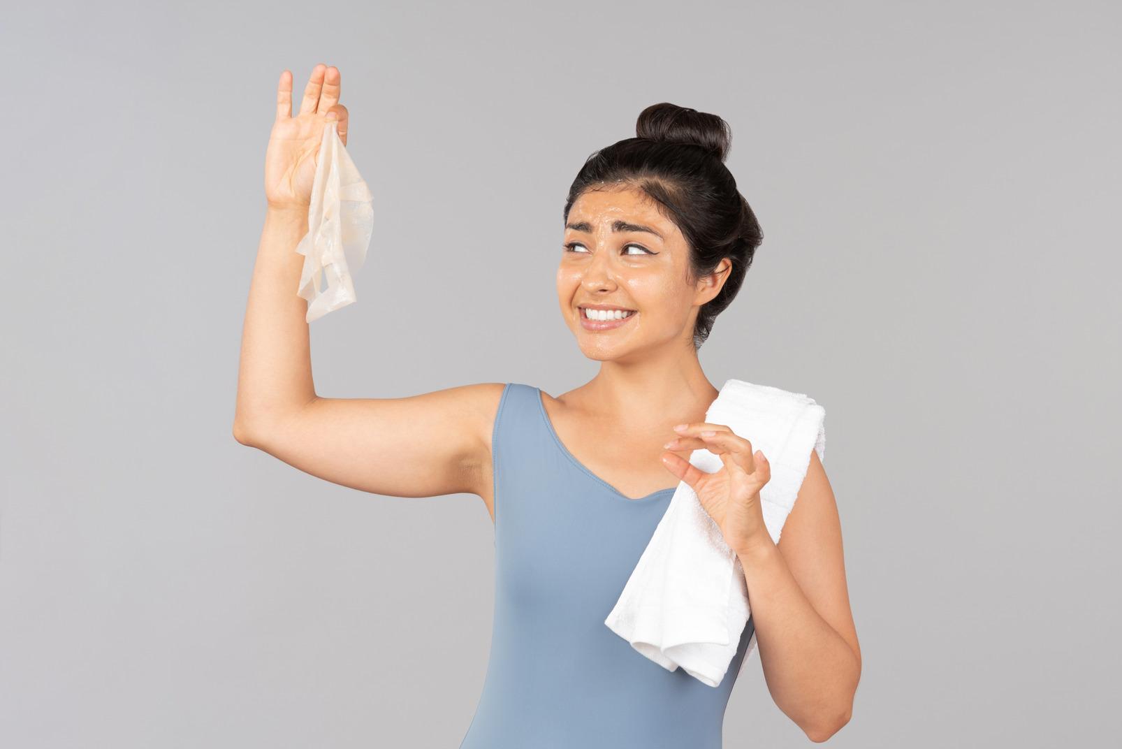 インドの女性の肩にマスクと白いタオルを保持