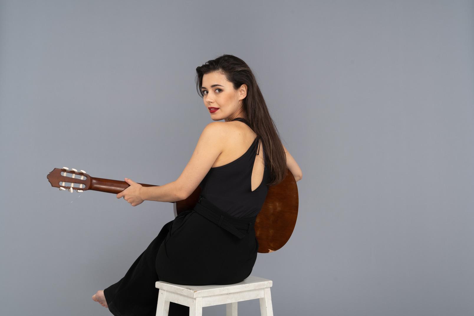 Rückansicht einer sitzenden jungen dame im schwarzen anzug, die die gitarre hält, während sie sich abwendet