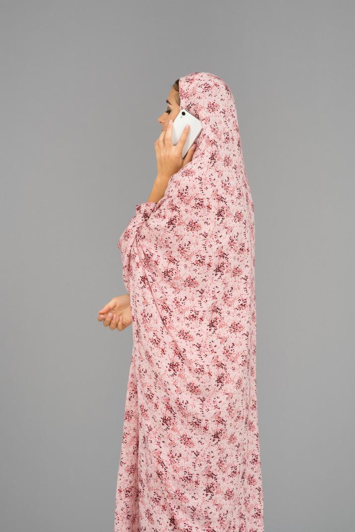 Frau in einem gebetskleid spricht am telefon