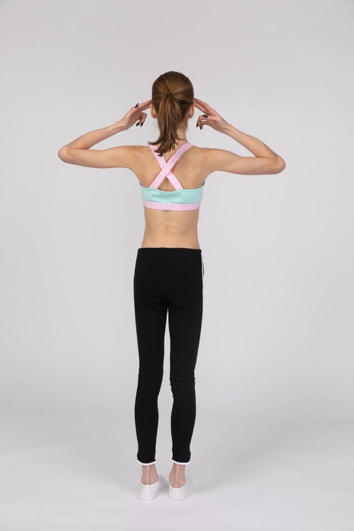 Back view of a teen girl in sportswear touching head