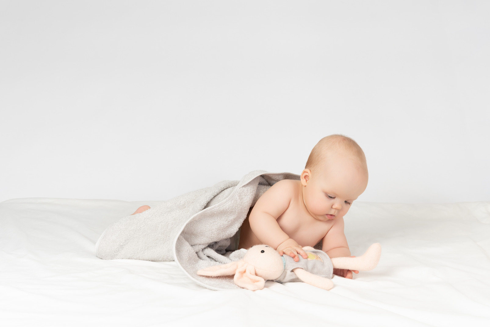 Baby in handtuch bedeckt und spielt mit spielzeug