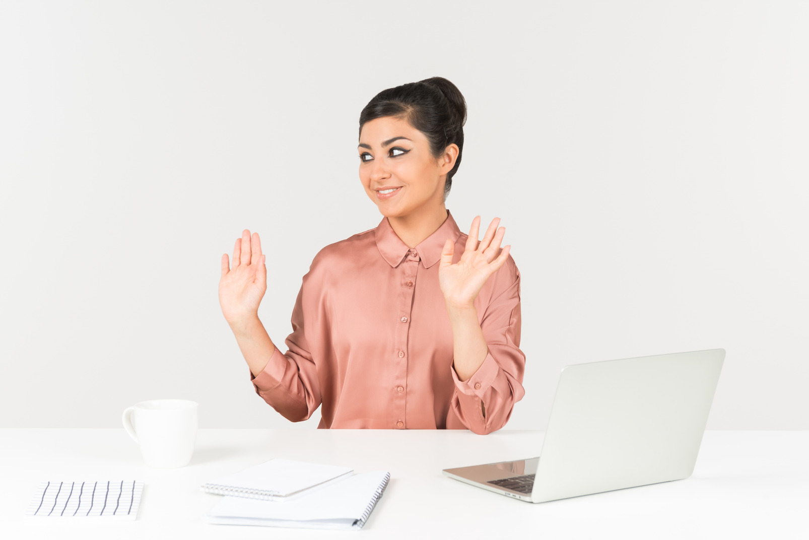 Young indian female office worker sitting at office desk with hands up