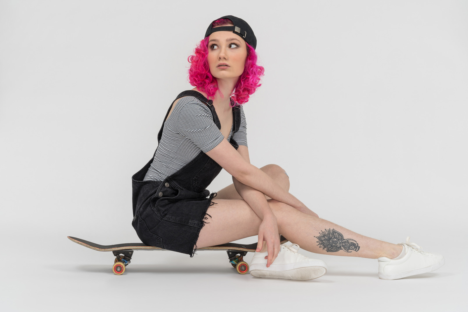 A pink haired girl sitting on a skateboard