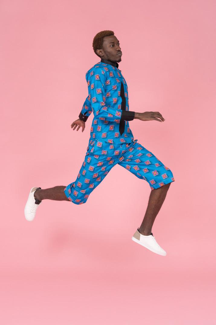 Black man in blue pajamas jumping on pink background