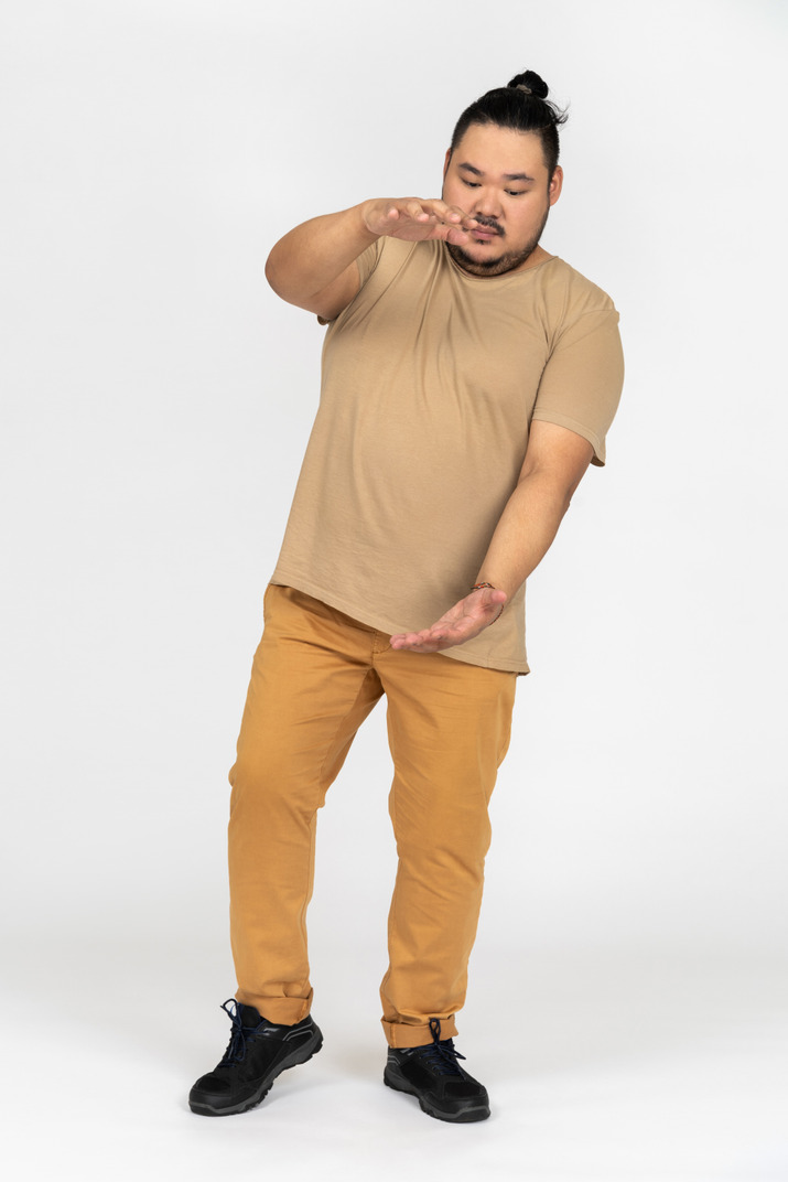Young asian man showing size with outstretched hands