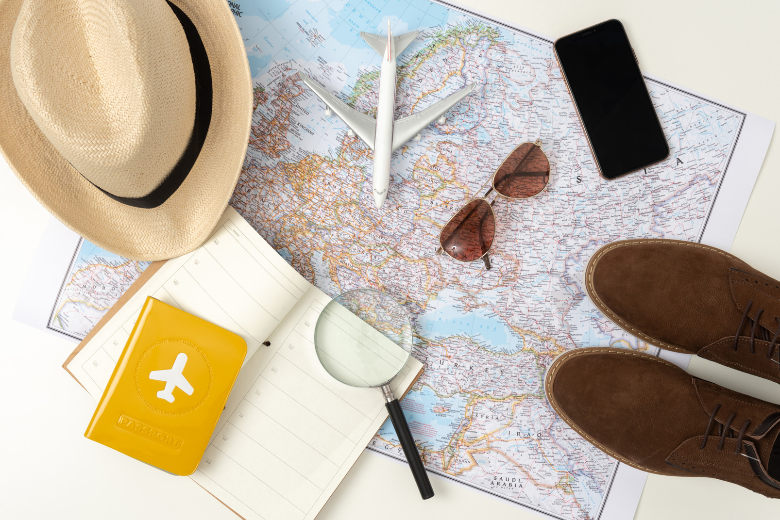 Your standard travel kit (don't forget the plain!), with the straw hat, comfortable boots, smartphone and sunglasses