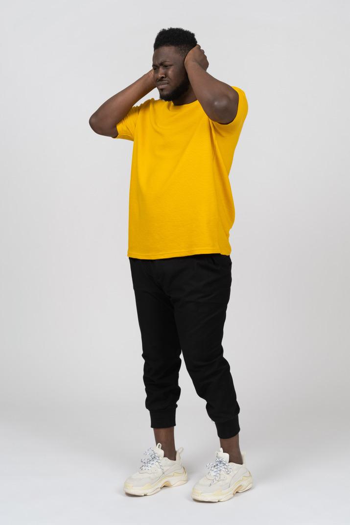 Vue de trois quarts d'un homme à la peau foncée en t-shirt jaune bloquant ses oreilles