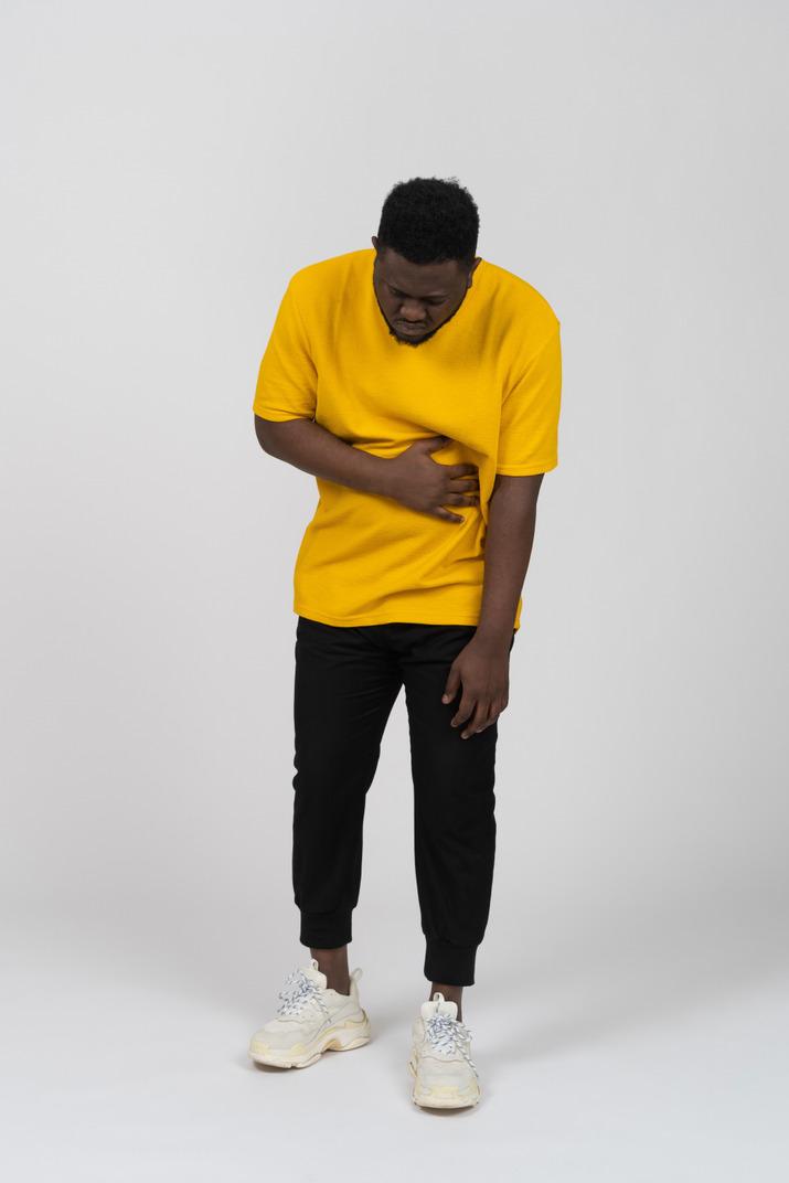胃に触れる黄色のtシャツを着た若い浅黒い肌の男の正面図