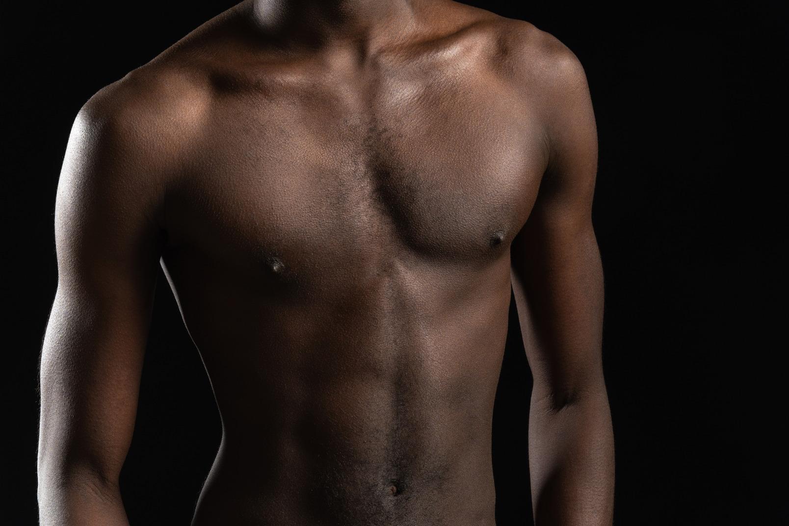 Nahaufnahme eines männlichen torsos im dunkeln