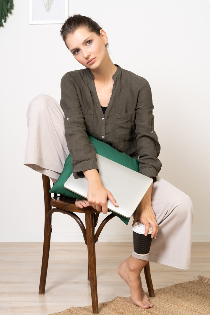 Front view of a young woman sitting on a chair and holding her laptop & touching coffee cup