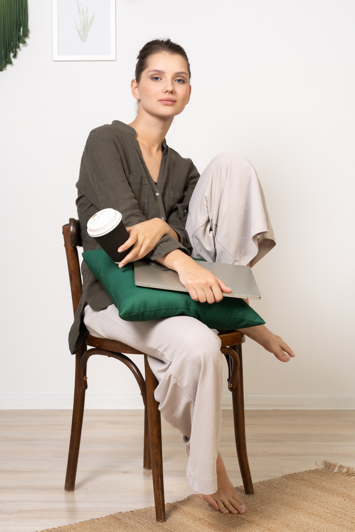 Three-quarter view of a young woman sitting on a chair and holding her laptop & touching coffee cup
