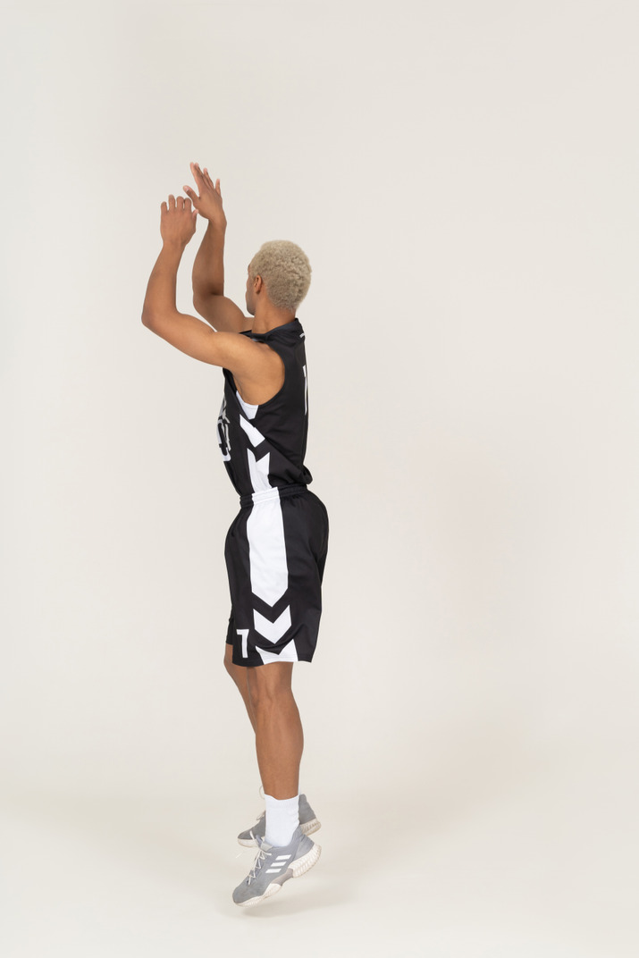 Side view of a young male basketball player throwing something