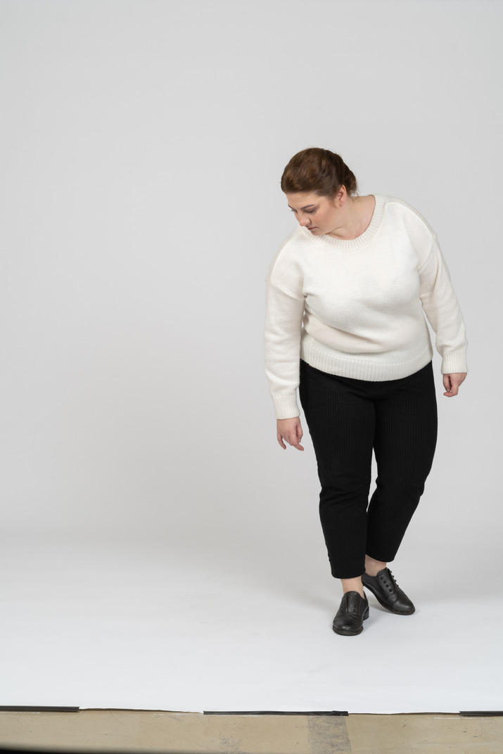 Front view of a plump woman in casual clothes looking down