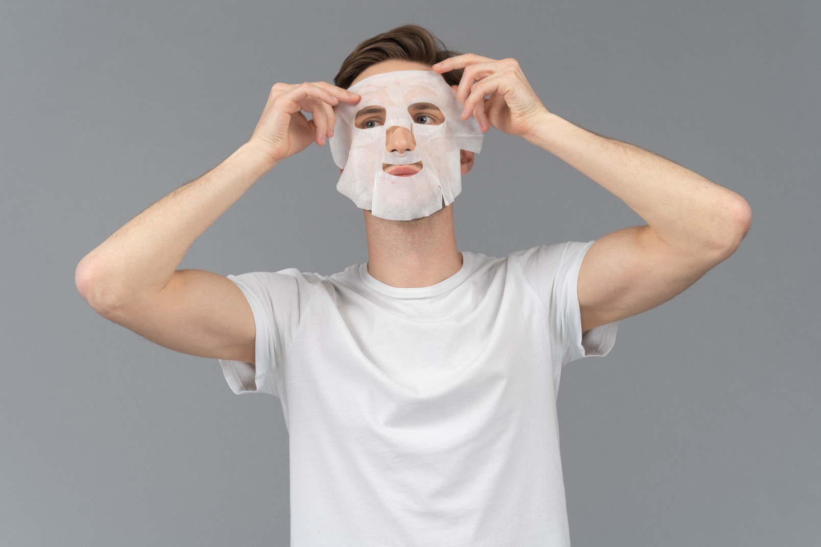 Front view of a young man putting on facial mask