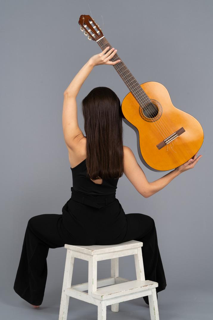 Rückansicht einer jungen dame im schwarzen anzug, die die gitarre über kopf hält und auf hocker sitzt