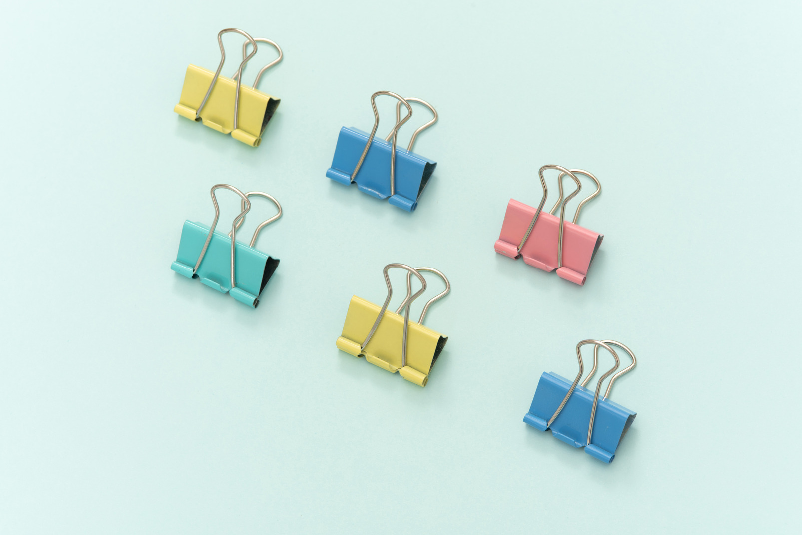 Colourful paper clips on blue background