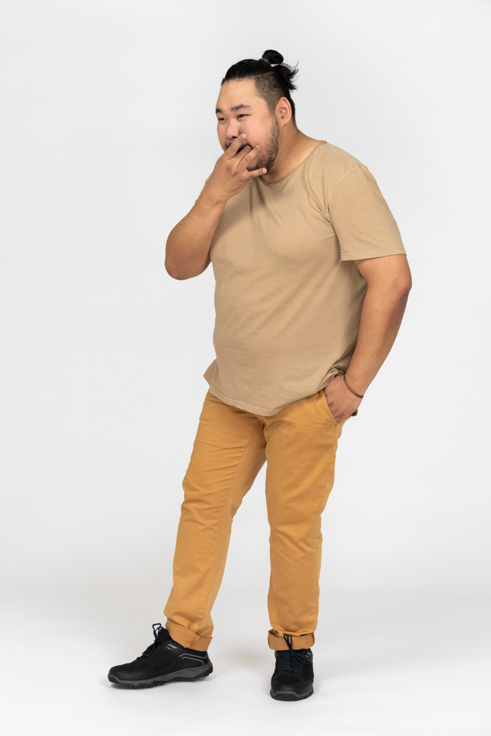 Plus size asian man using his fingers to whistle