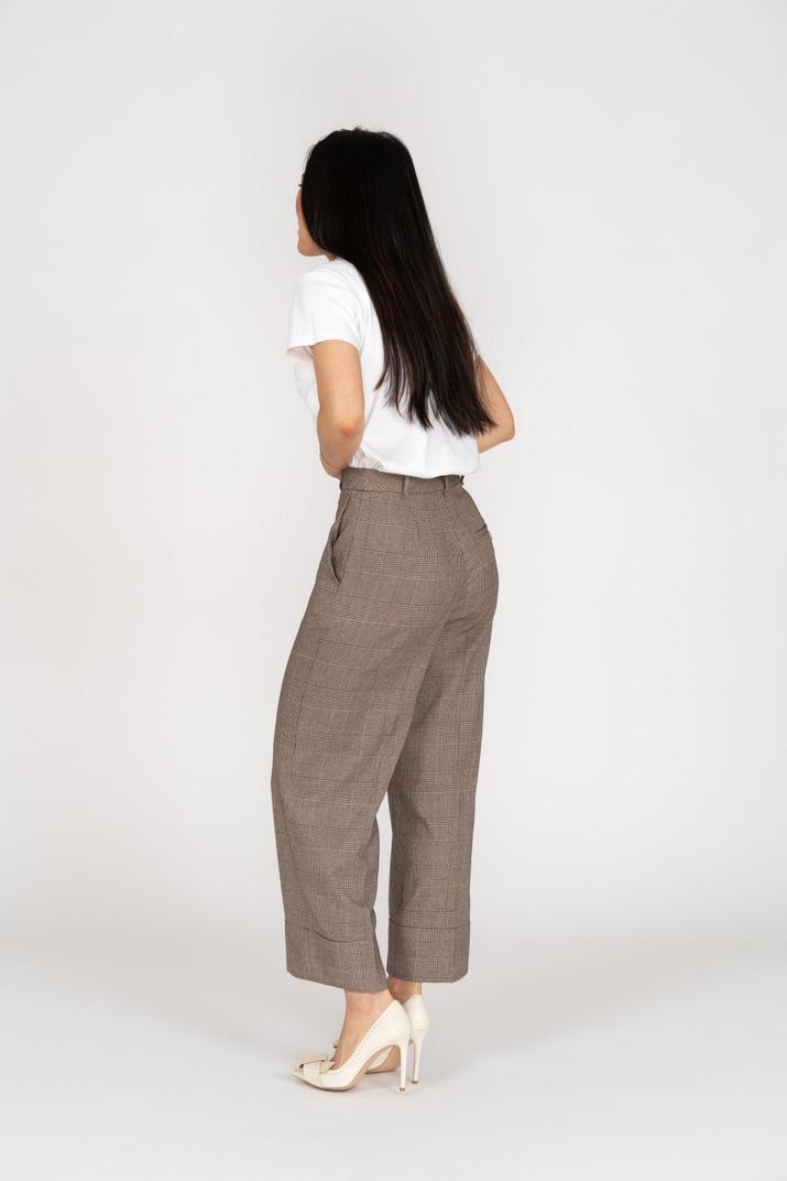 Dreiviertel-rückansicht einer jungen dame in reithose und t-shirt, die ihren bauch berührt