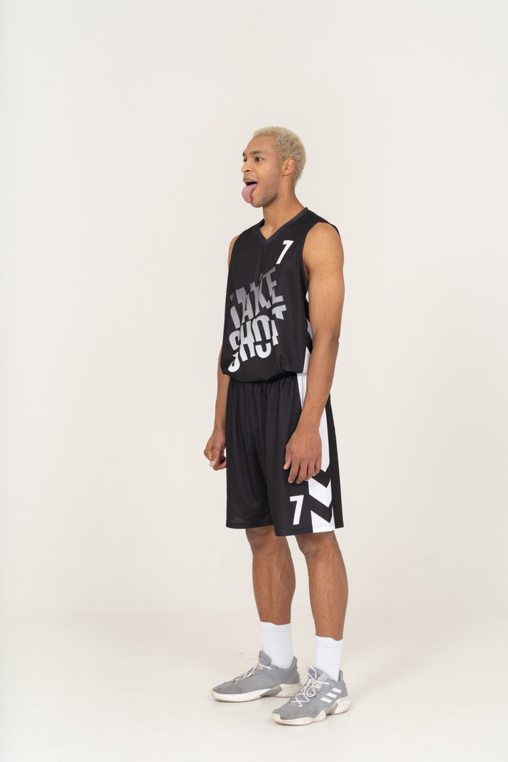 Three-quarter view of a crazy young male basketball player showing tongue