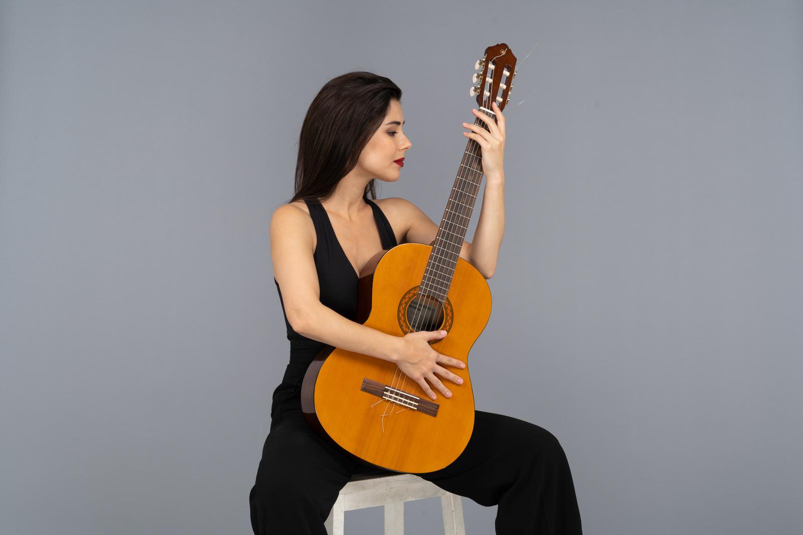 Vorderansicht einer sitzenden jungen dame im schwarzen anzug, die ihre gitarre betrachtet