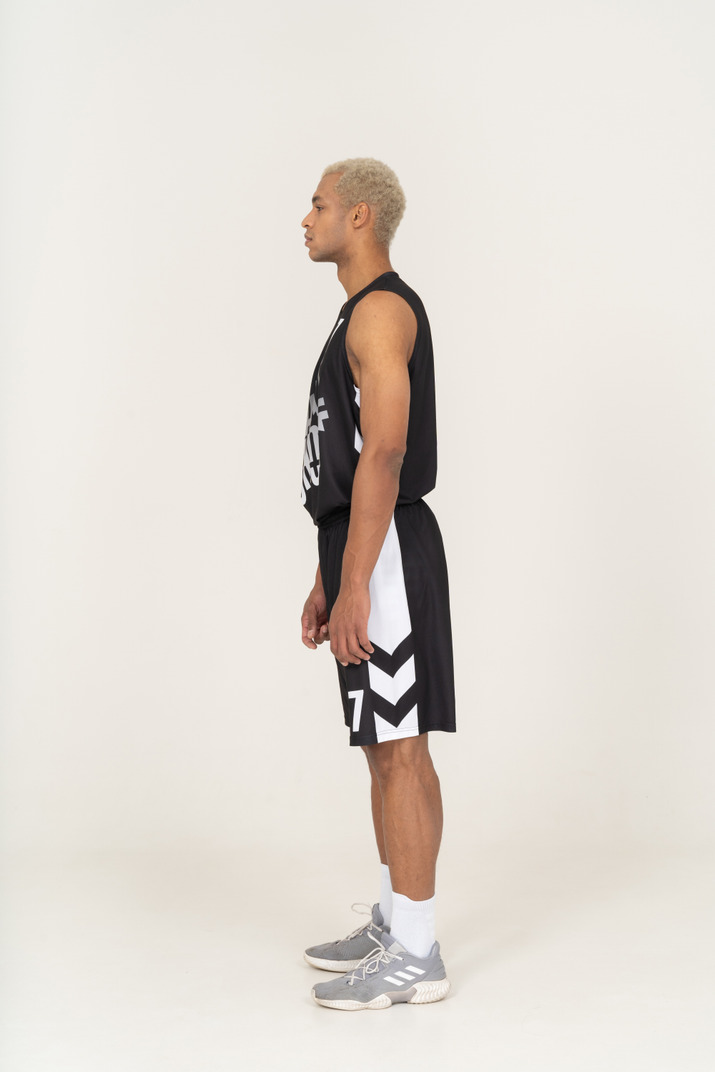 Side view of a young male basketball player standing still