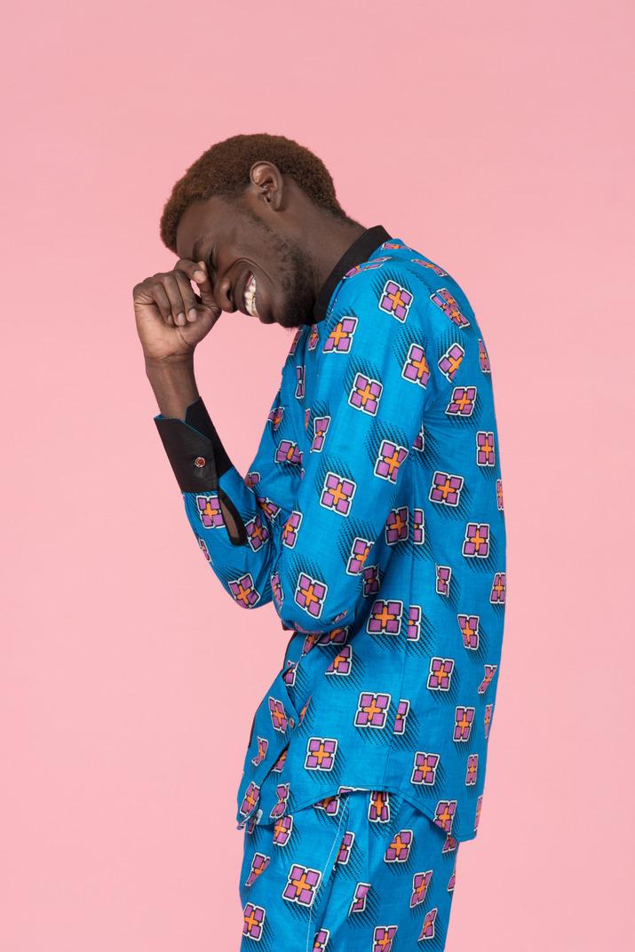 Black man in blue pajamas laughing